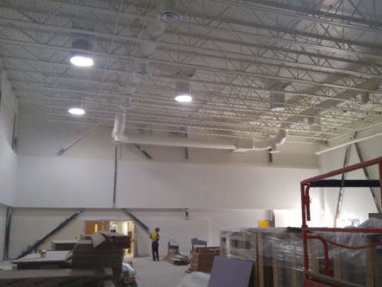 Gym walls and ceiling painted white with hanging lights installed and on and a construction worker looking on