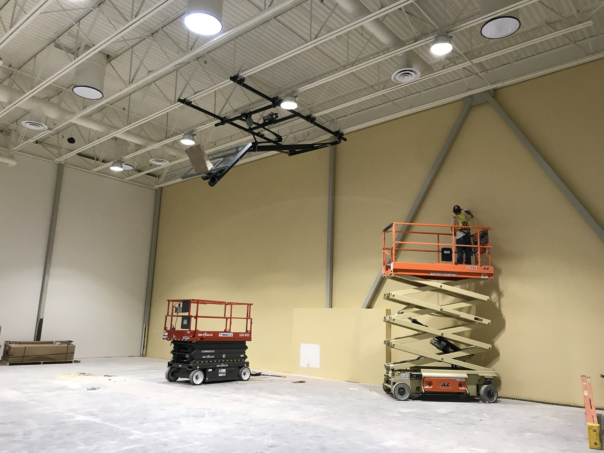 Interior of gym with worker on cherry picker truck and basketball hoop extended