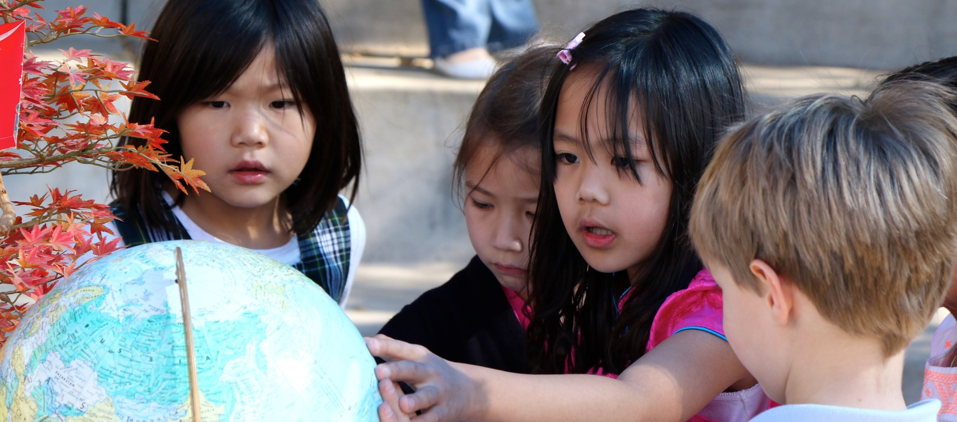 Students looking at a globe.