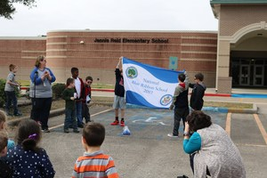 Students holding National Blue Ribbon School flag while people look on.