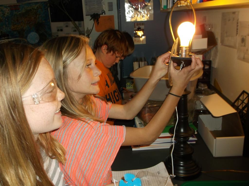 Students hold up a light bulb as they learn about energy in science class.