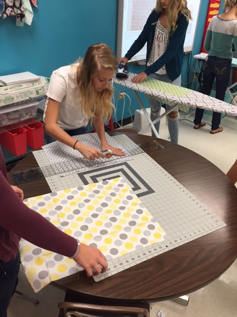 East Wilkes High students measure and cut fabric