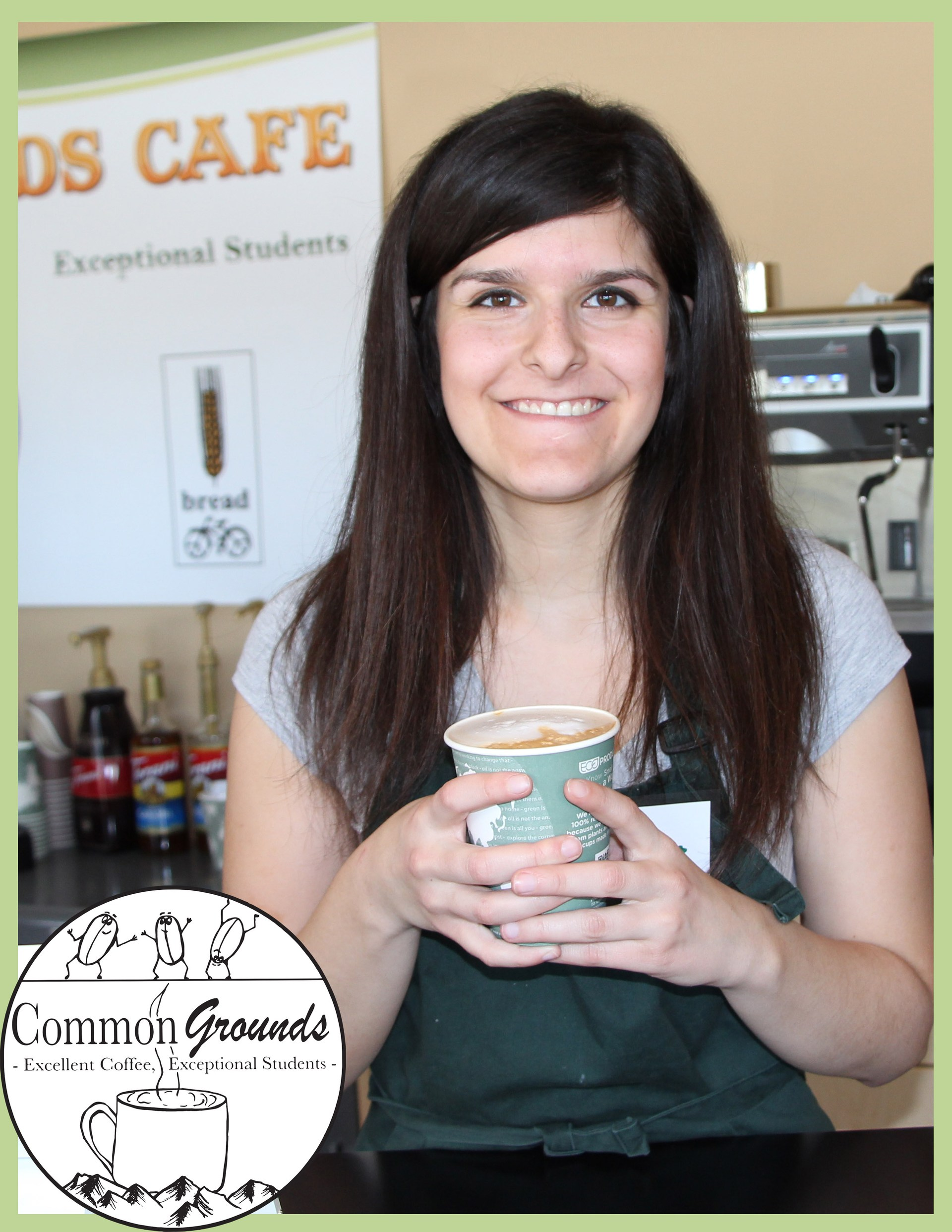 Student holds a latte at Common Grounds Cafe