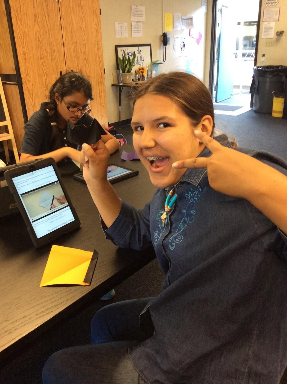 Student on iPad working on a project and giving us a candid peace sign!