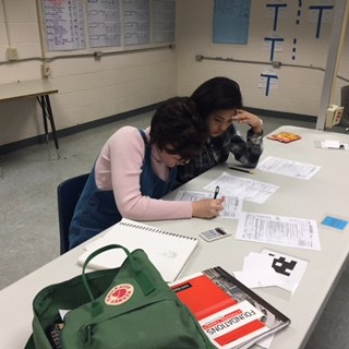 two students at table working on taxes