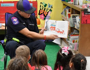 Fireman reading to elementary students.