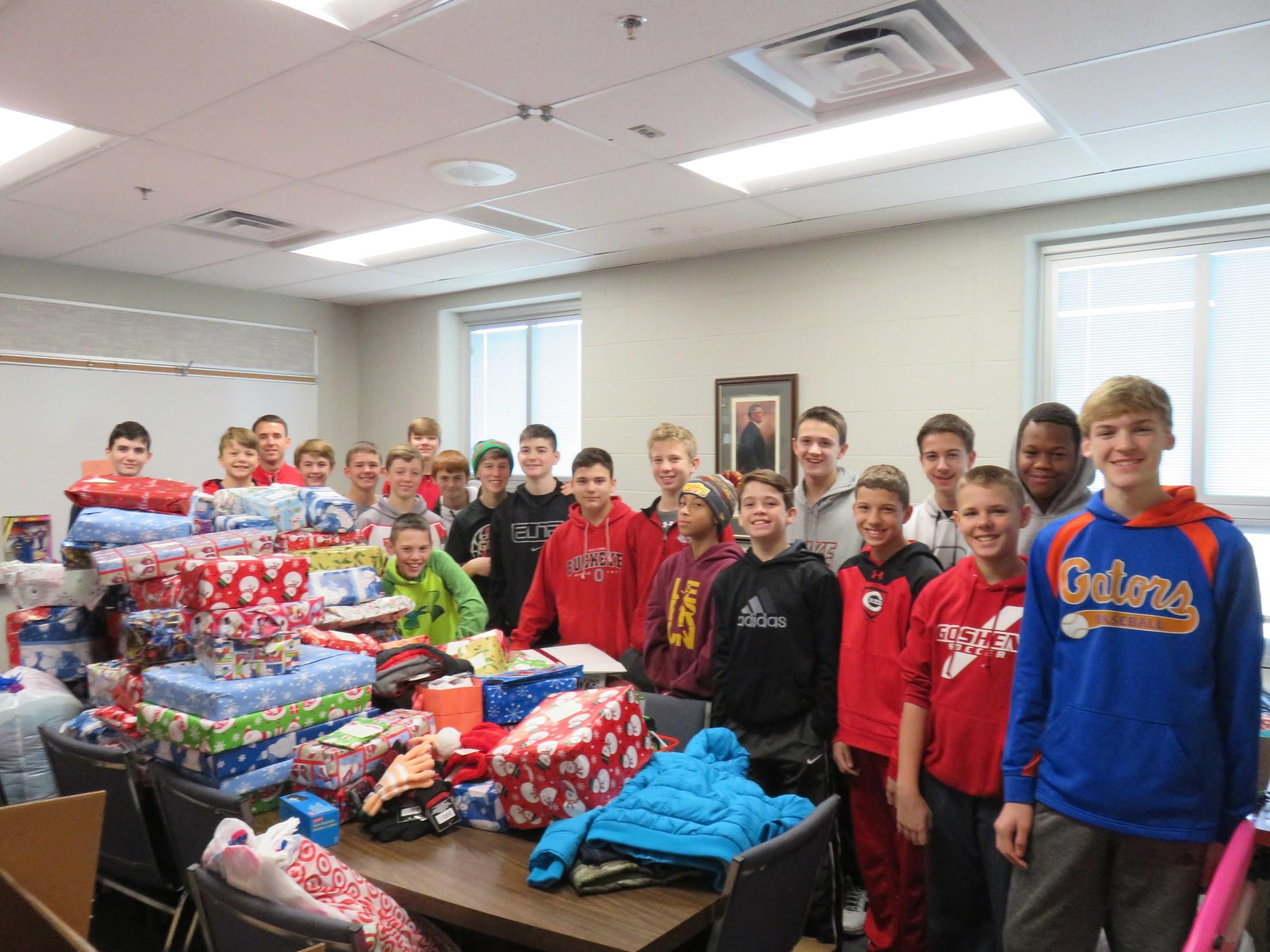 Boys basketball team wrapping Christmas gifts