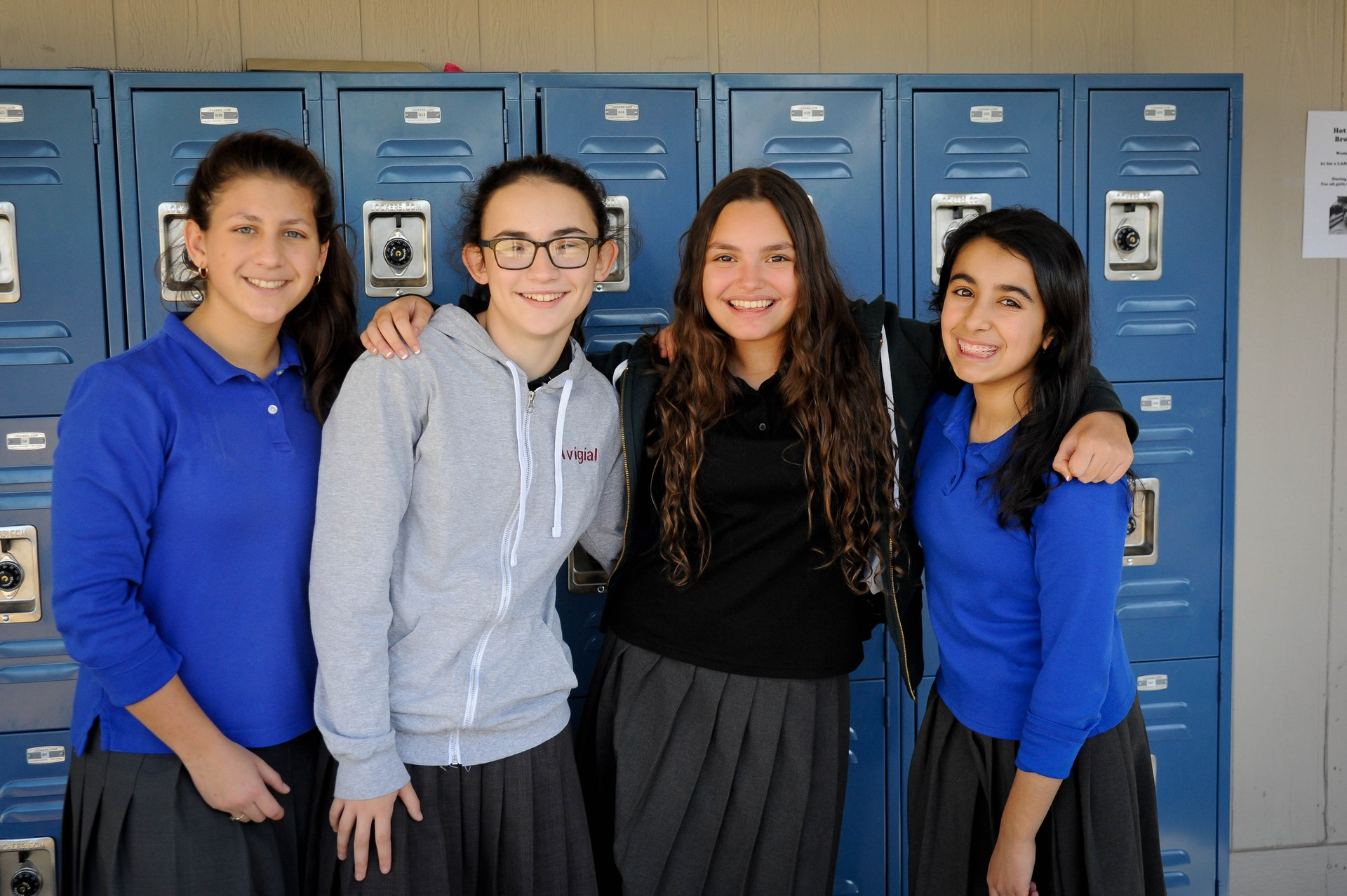girls smiling in front of lockers