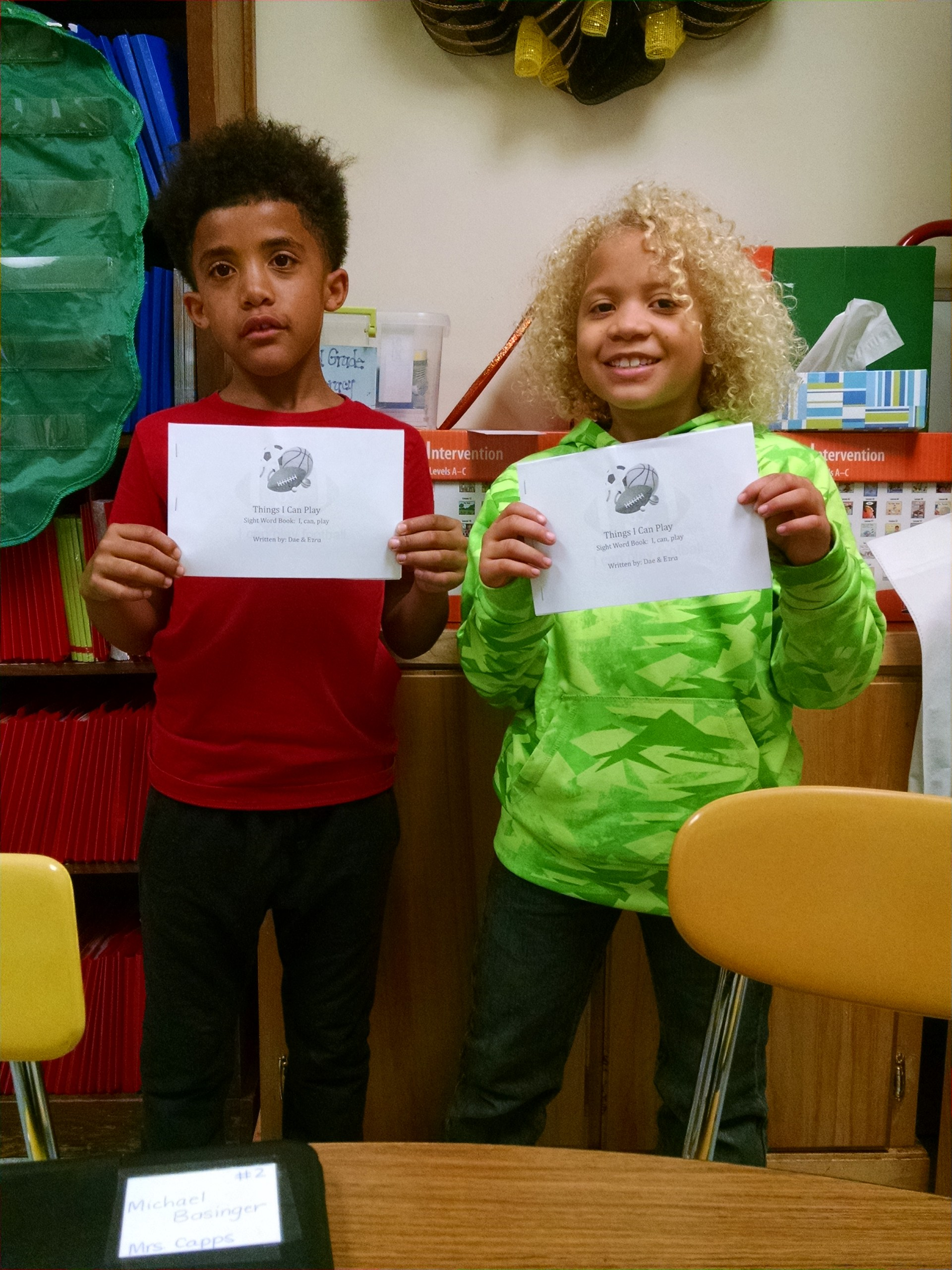 This is a picture of Dae and Ezra holding the book that they wrote called, 'Things I Can Play.'