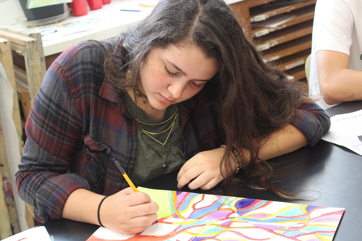 Sam Irgang paints a watercolor tree during advanced art