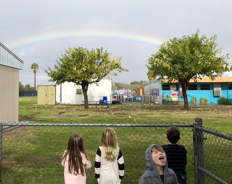 kindergarteners looking at a rainbow