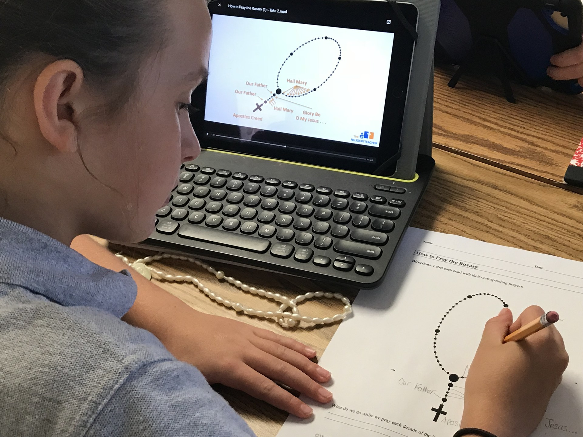 Student using iPad to complete rosary assignment