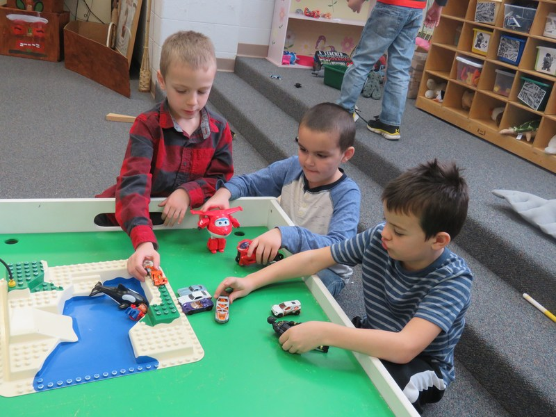A group of boys play with cars and trucks.