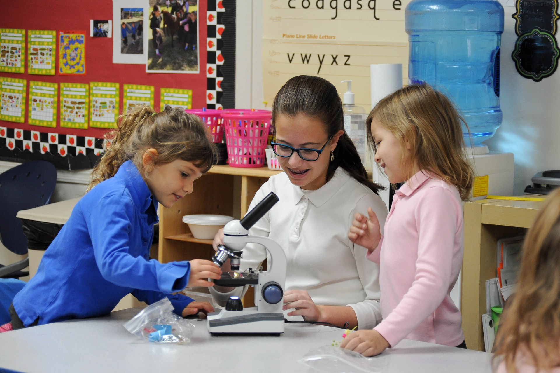 middle school girls teaching kindergarten girls how to use a microscope