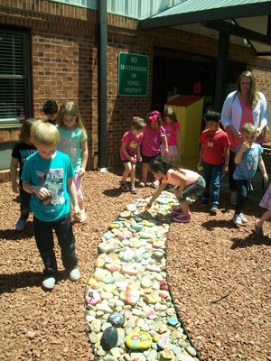 Students add decorated rocks to river bed.