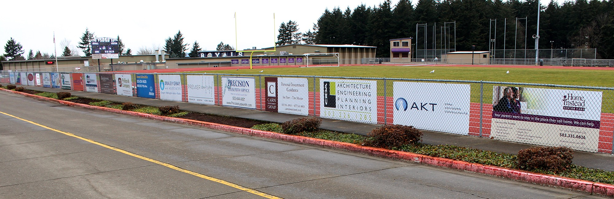 Business Sponsor logos on the track & field fencing