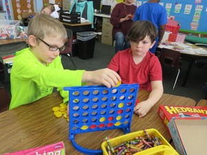 Two first grade boys play a game of Connect Four.