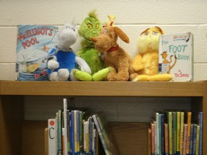 Dr. Seuss books and stuffed animals are on top of a bookshelf in the library.