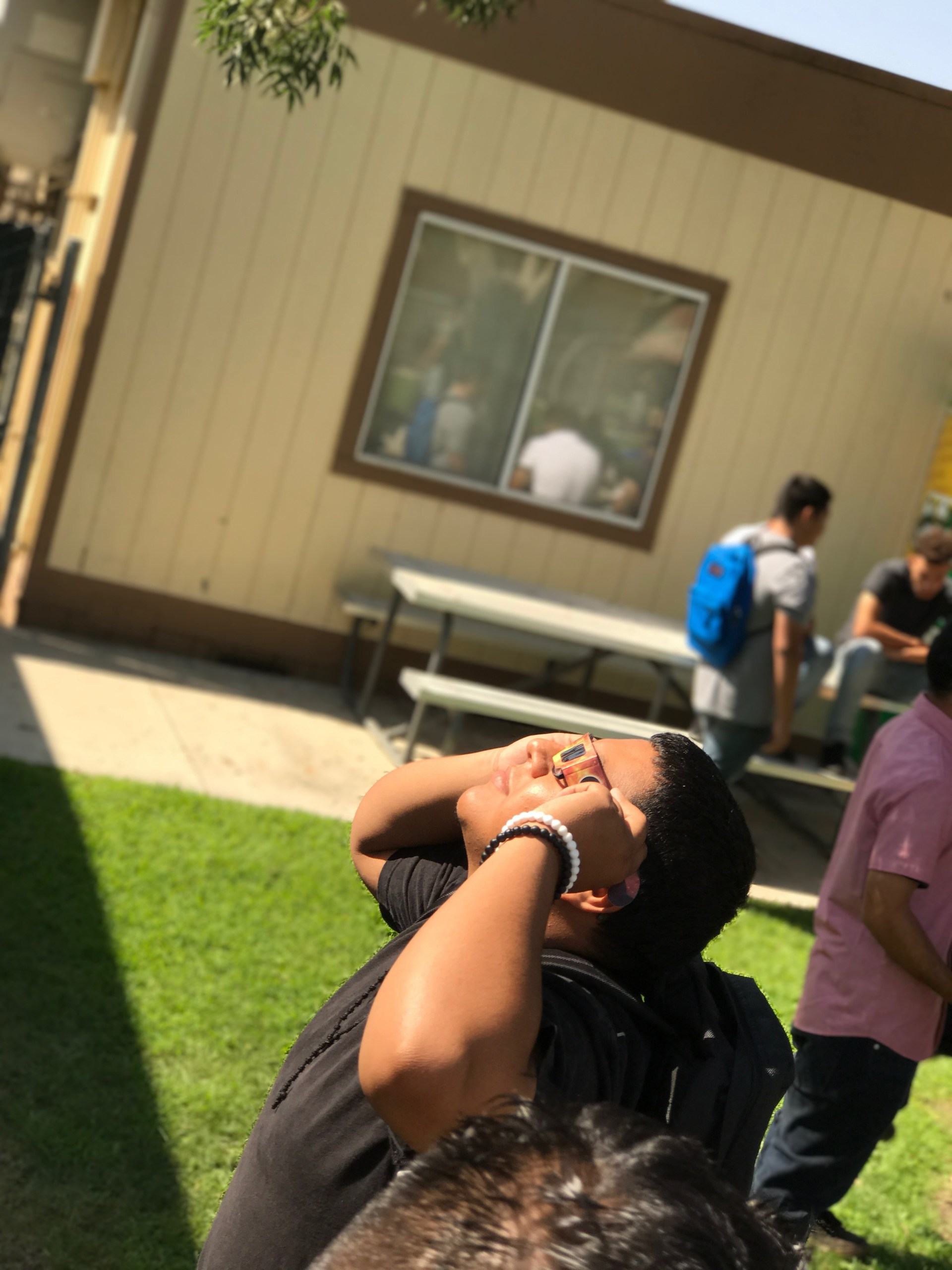 A student observes the solar eclipse