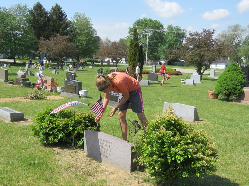 An 8th grader places a flag on a grave site of a U.S. Veteran.