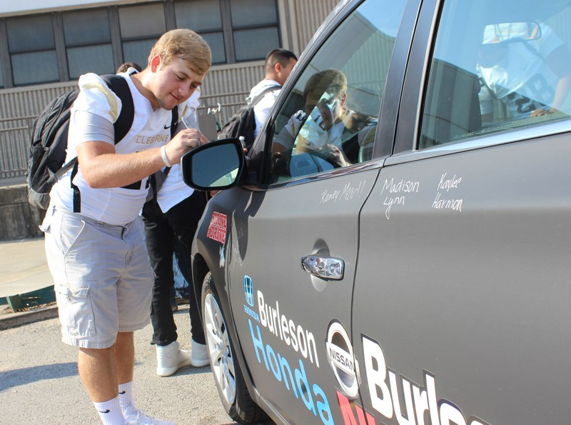 CHS student signing wrapped car to be given away in attendance incentive program
