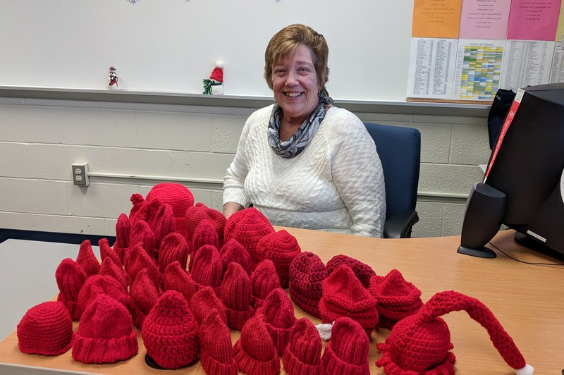 Mrs. Laws and the red hats she knitted with her mom and friend.