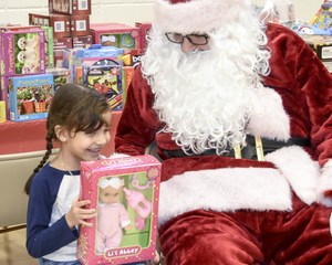 Young girl getting a new doll from Santa Claus