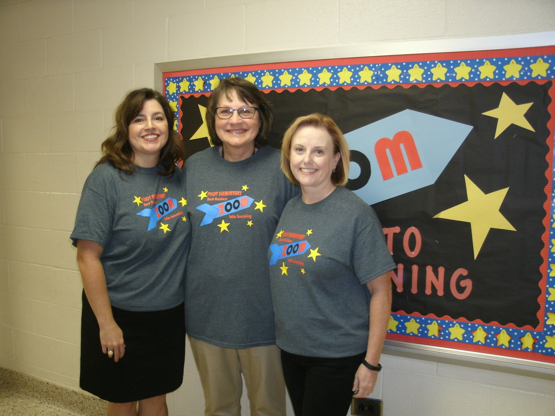 Three Title 1 teachers are standing in front of a bulletin board.