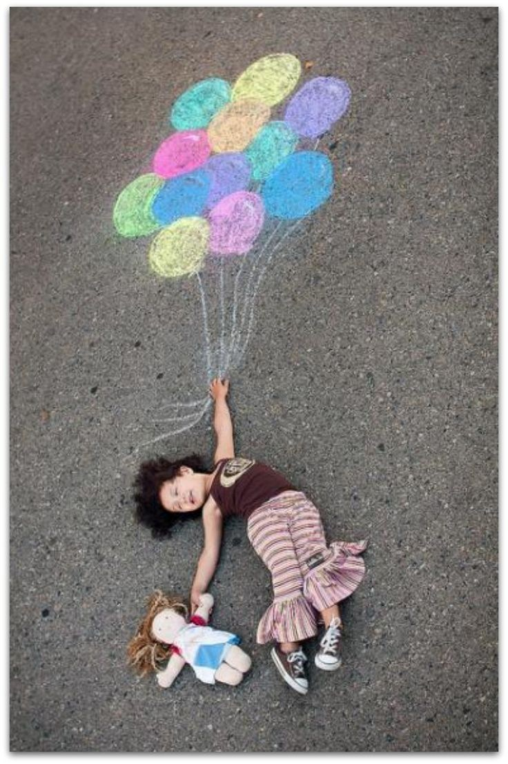 child holding chalk drawing of balloons