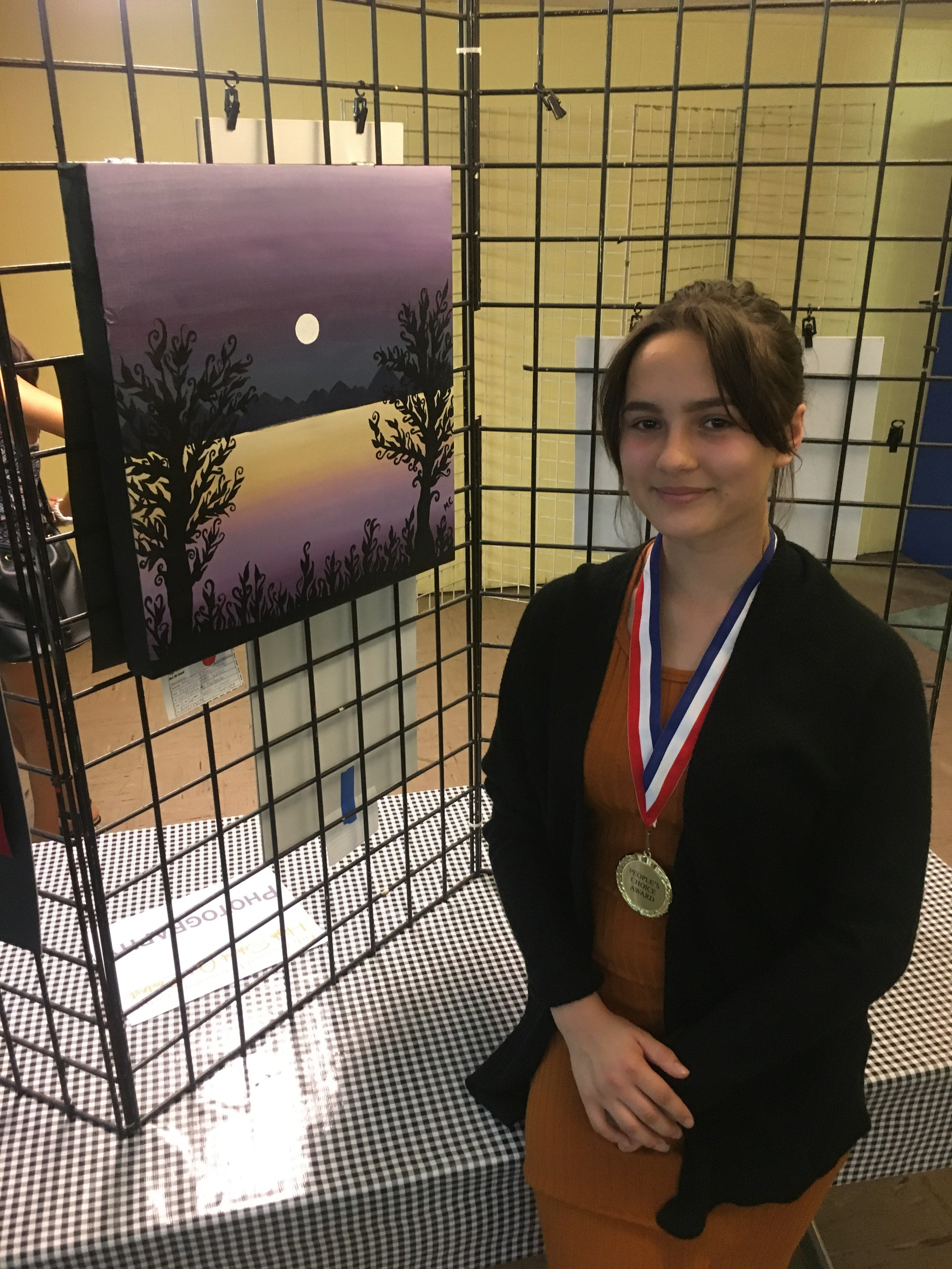 Student with winning artwork at the Harmony Center Art show