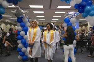 Students walking with their diplomas.
