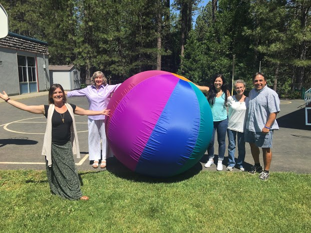 Five people standing around giant inflated ball