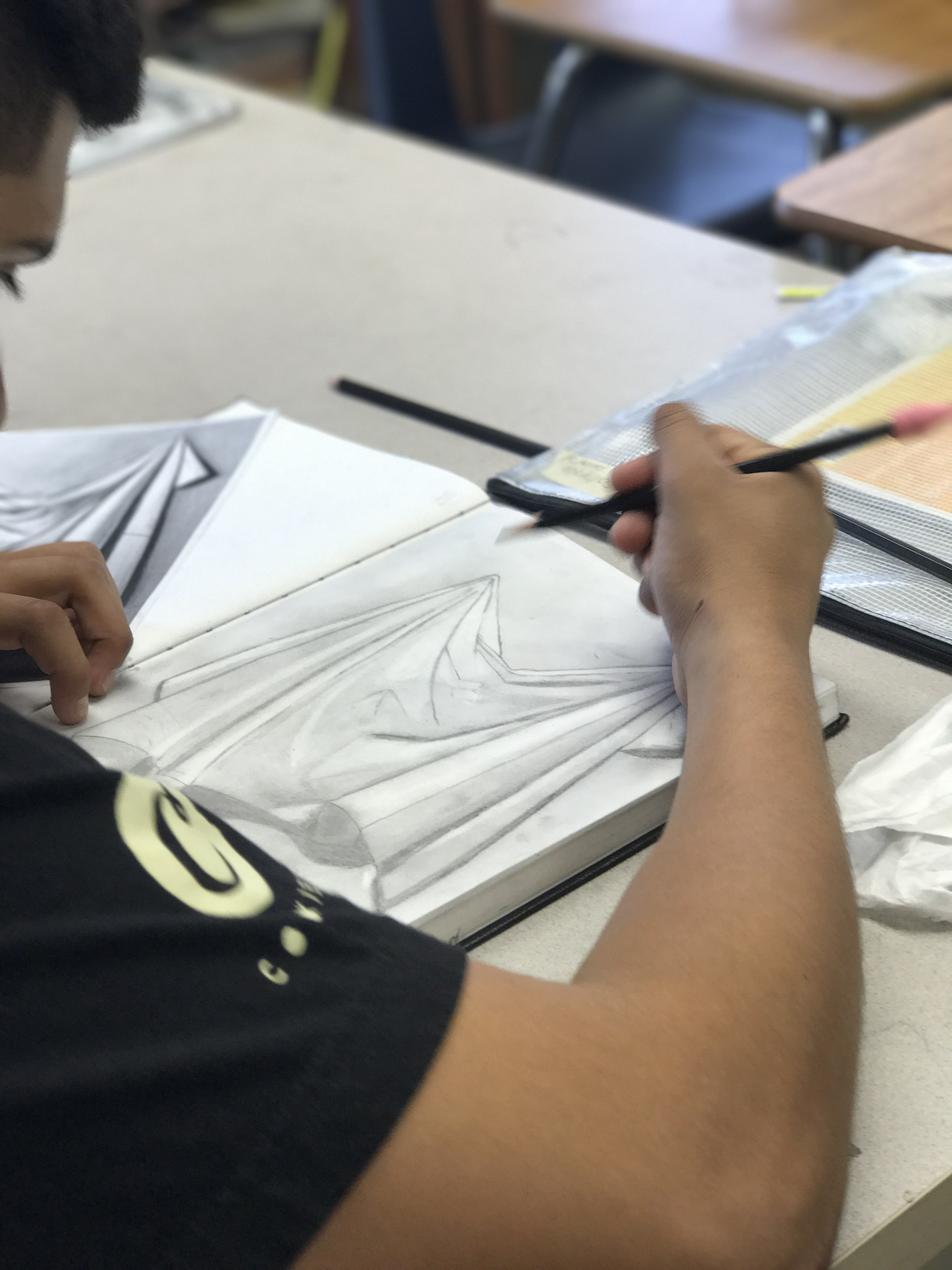 Student studies the folds and shading of a fabric drawing