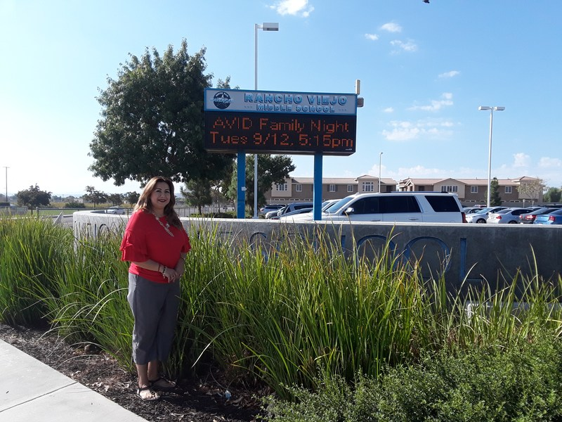 Enriqueta Armenta in front of a Rancho Viejo sign.