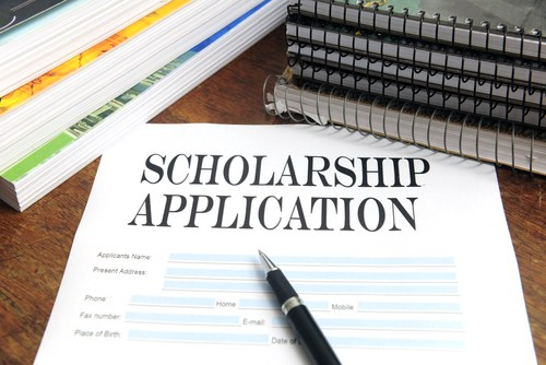 image of scholarship application, books and pen