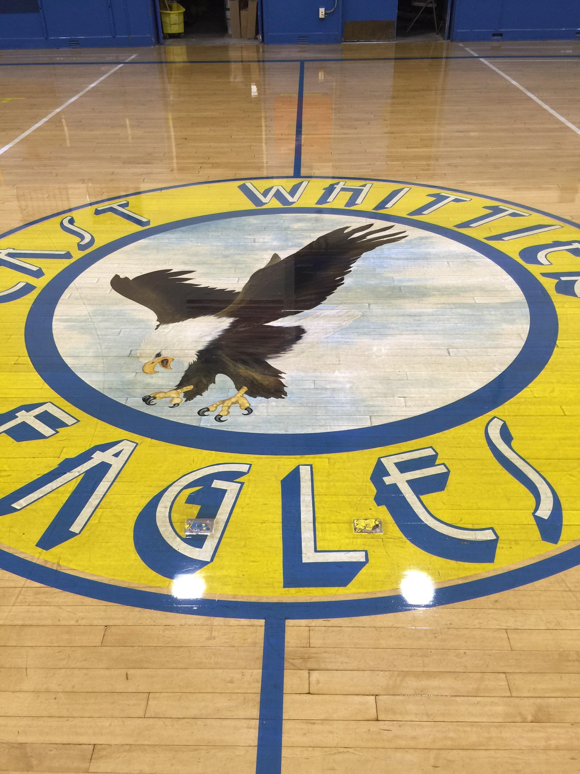 East Whittier Middle School logo on gym floor after waxing.