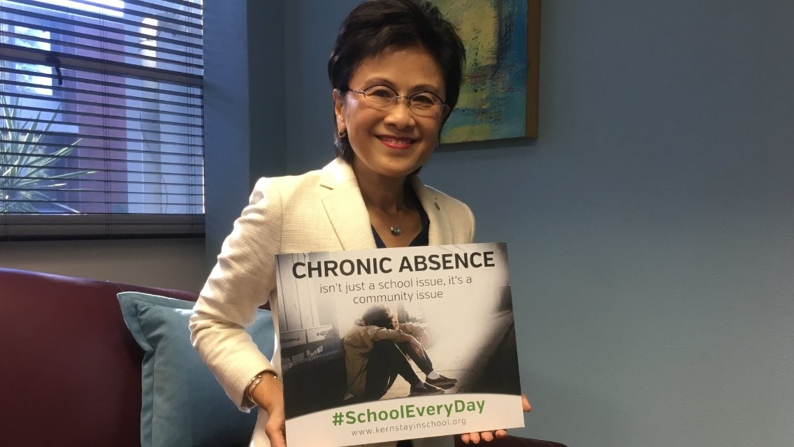 Mayor holding a chronic absence sign