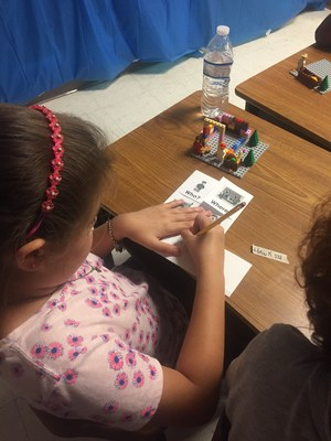 Image: student using Legos to create a story line and write a comic strip