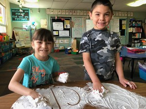 Students practicing letters with shaving cream.