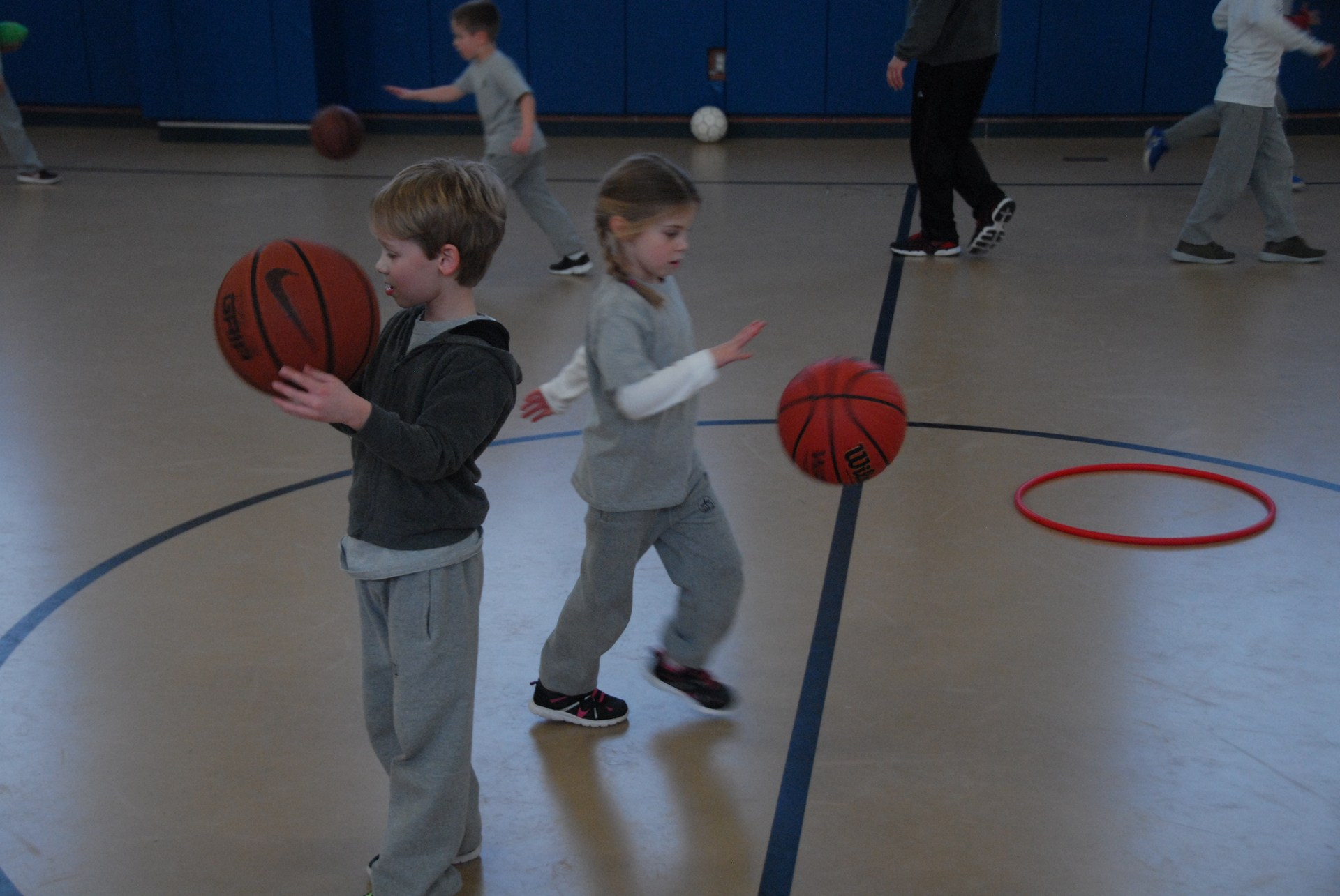 Two students play basketball during class
