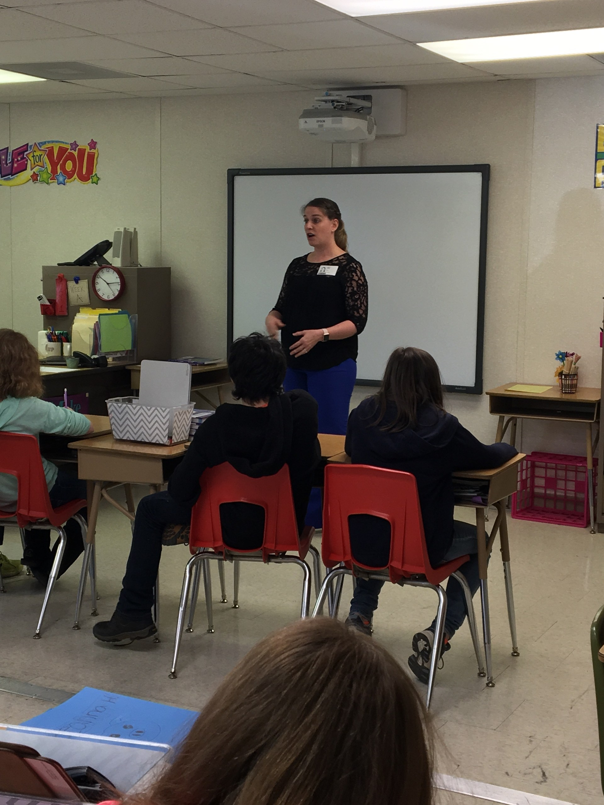 Sixth Grade students sit in desks and listen to guest speaker in front of class.