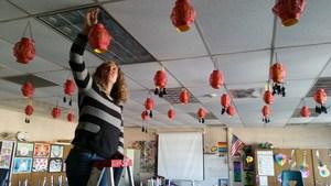 Ms. Wallace hanging Chinese Lanterns.