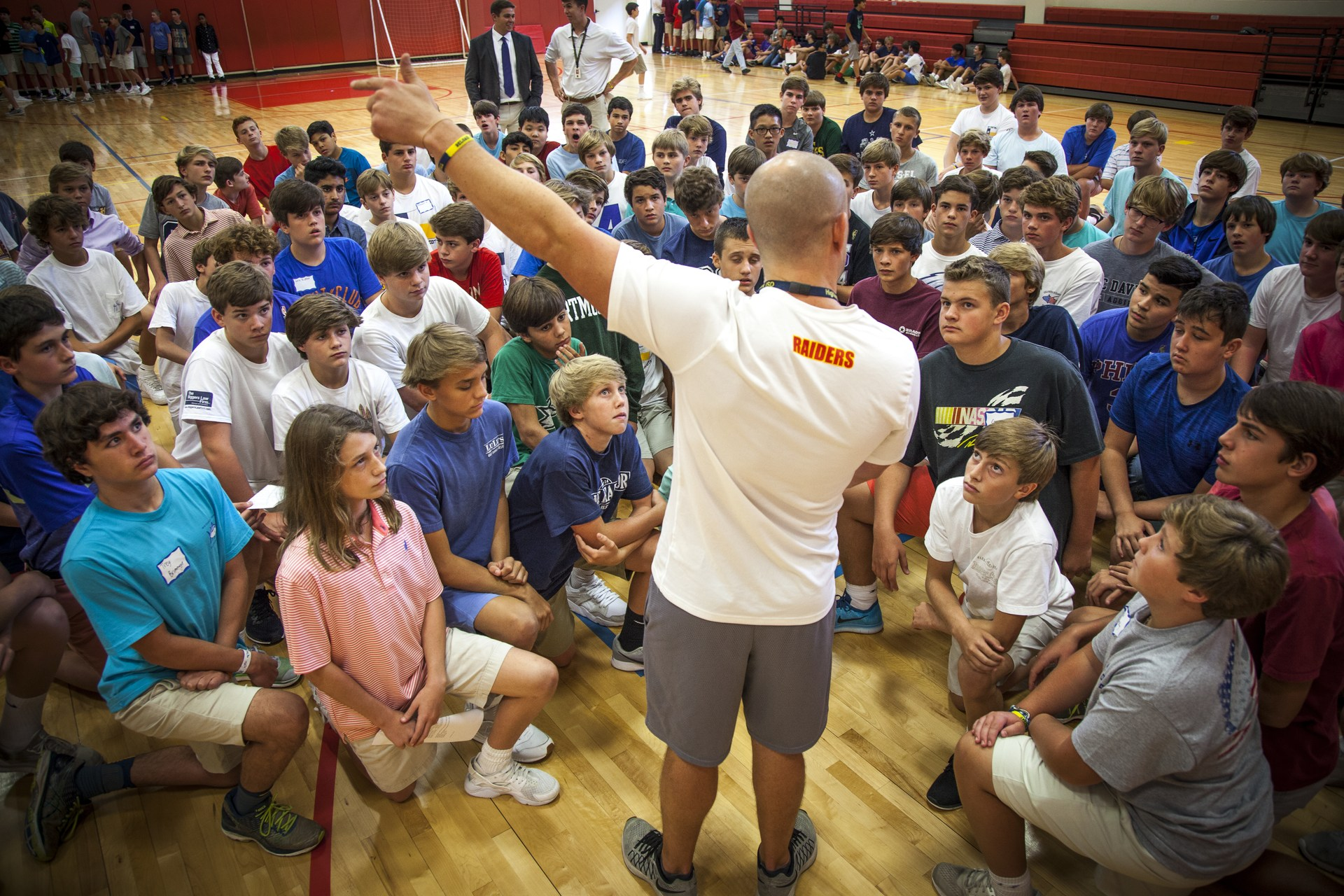 A coach talks with his students in the gymnasium.