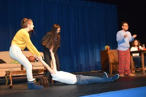 Teenagers dragging a man across a stage.