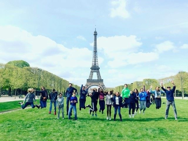 students jumping in air in front of Eiffel Tower