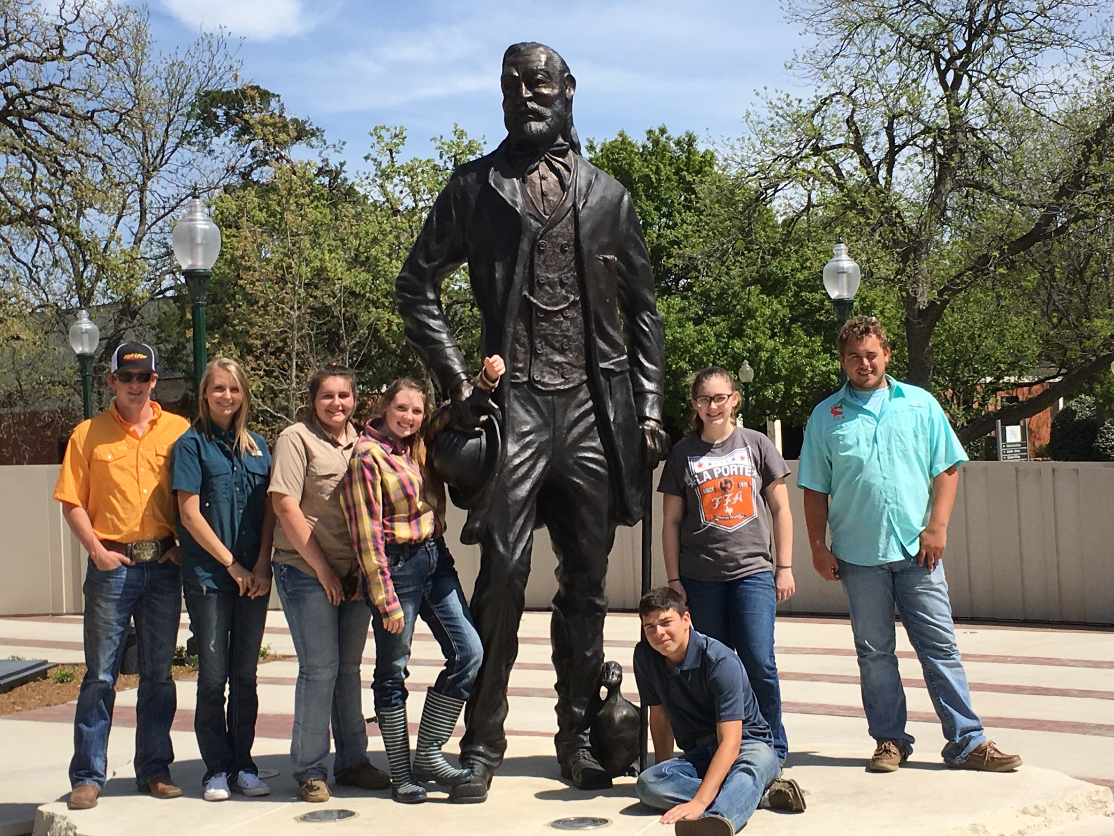 Ag students and teacher posing in front of statue