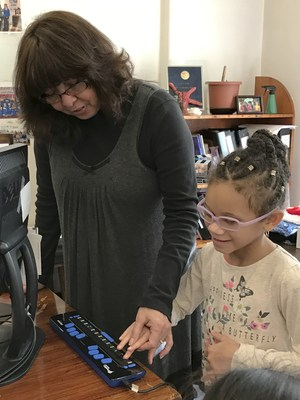 Student playing braille game on braille display
