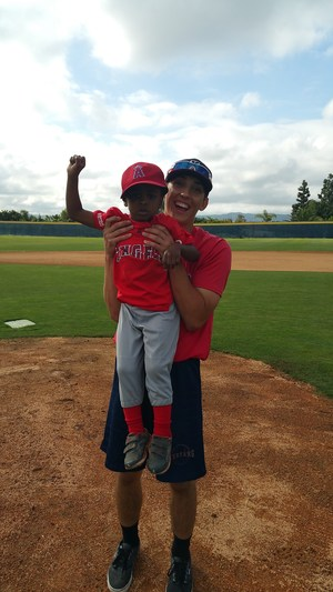 YLHS player lifting up a pony league player