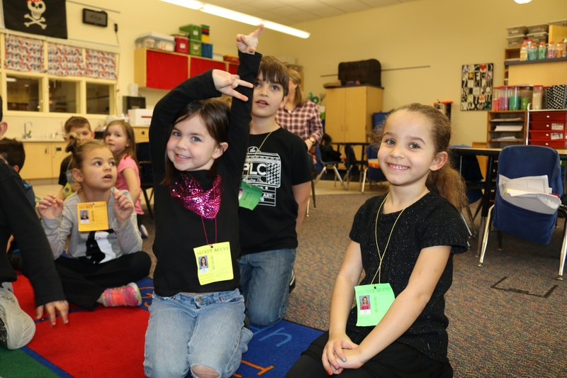 girl raising hand while her friends smile in kindergarten sitting on floor
