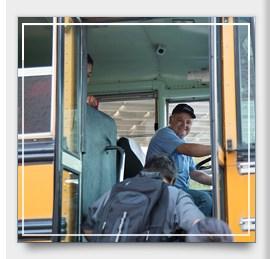 Bus Driver Smiling through open bus door